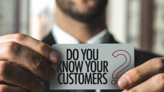 "man holding card that says ""do you know your customers"
